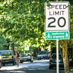 "Woman riding bike on street with car parking and 20 mph speed limit and ""Neighborhood Greenway"" signs."