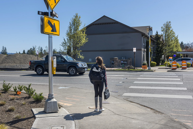Person waiting at marked crosswalk